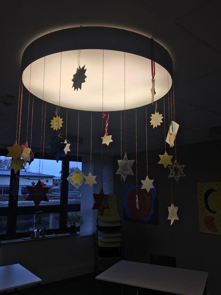 Auf dem Foto hängen viele gebastelte Papiersterne an einer Lampe.