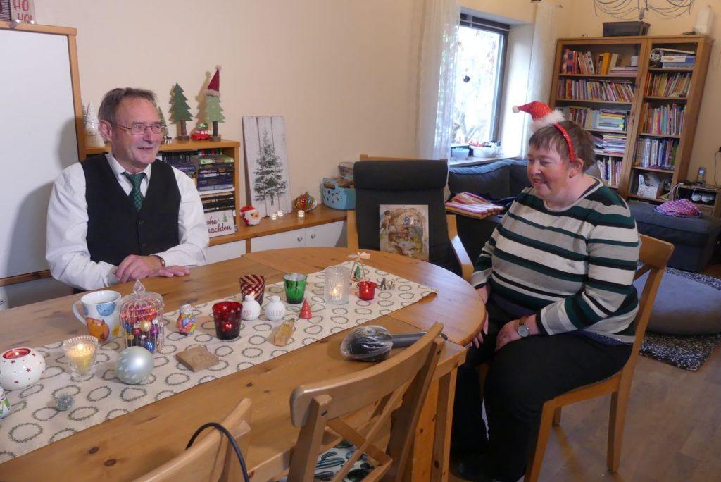 Auf dem Foto sitzen Josef Schmaußer und Silvia Stiegler an einem weihnachtlich geschmückten Tisch und bereiten sich auf das Interview vor. Beide lachen.
